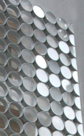 Photo: Corner detail of the Design Hub. A double-skin façade with a unique external skin that incorporates glazing disks. The disks in the outer façade have the capacity to be fitted with photovoltaic collectors for harnessing solar power.